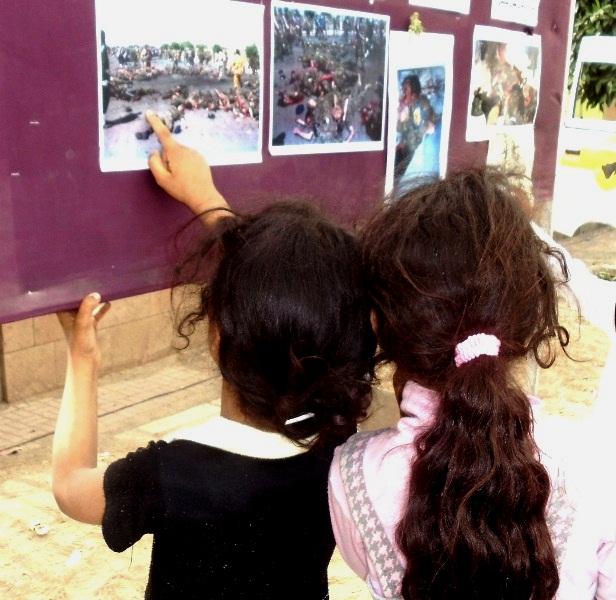 فتاتان يمنيتان بمعرض لصور الشهداء بصنعاء